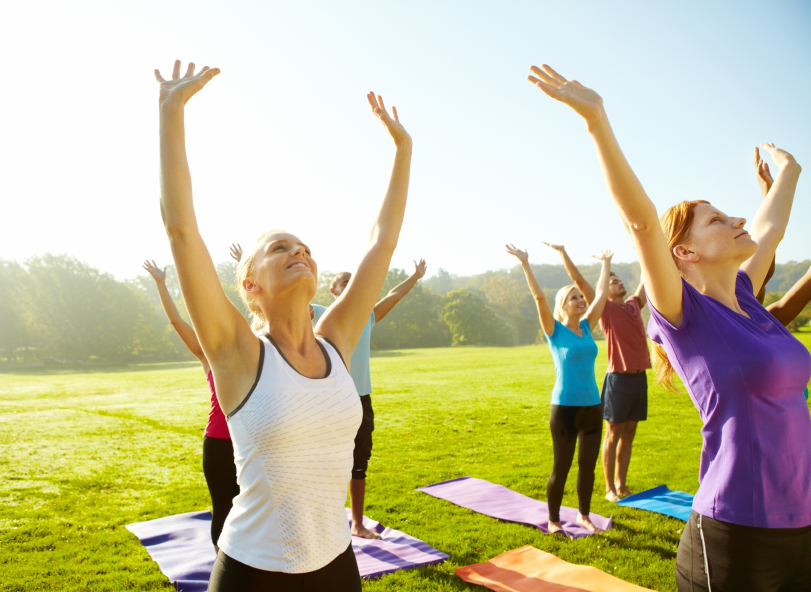 Group of people reaching toward the skies as they do their yoga class outdoors