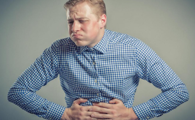 man-in-blue-shirt-with-stomach-pain-825x510
